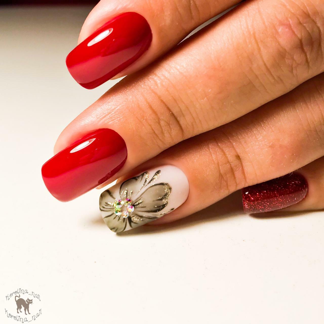 Маникюр с цветочным рисунком, стразами и блестками в бордовом цвете на длинные ногти.