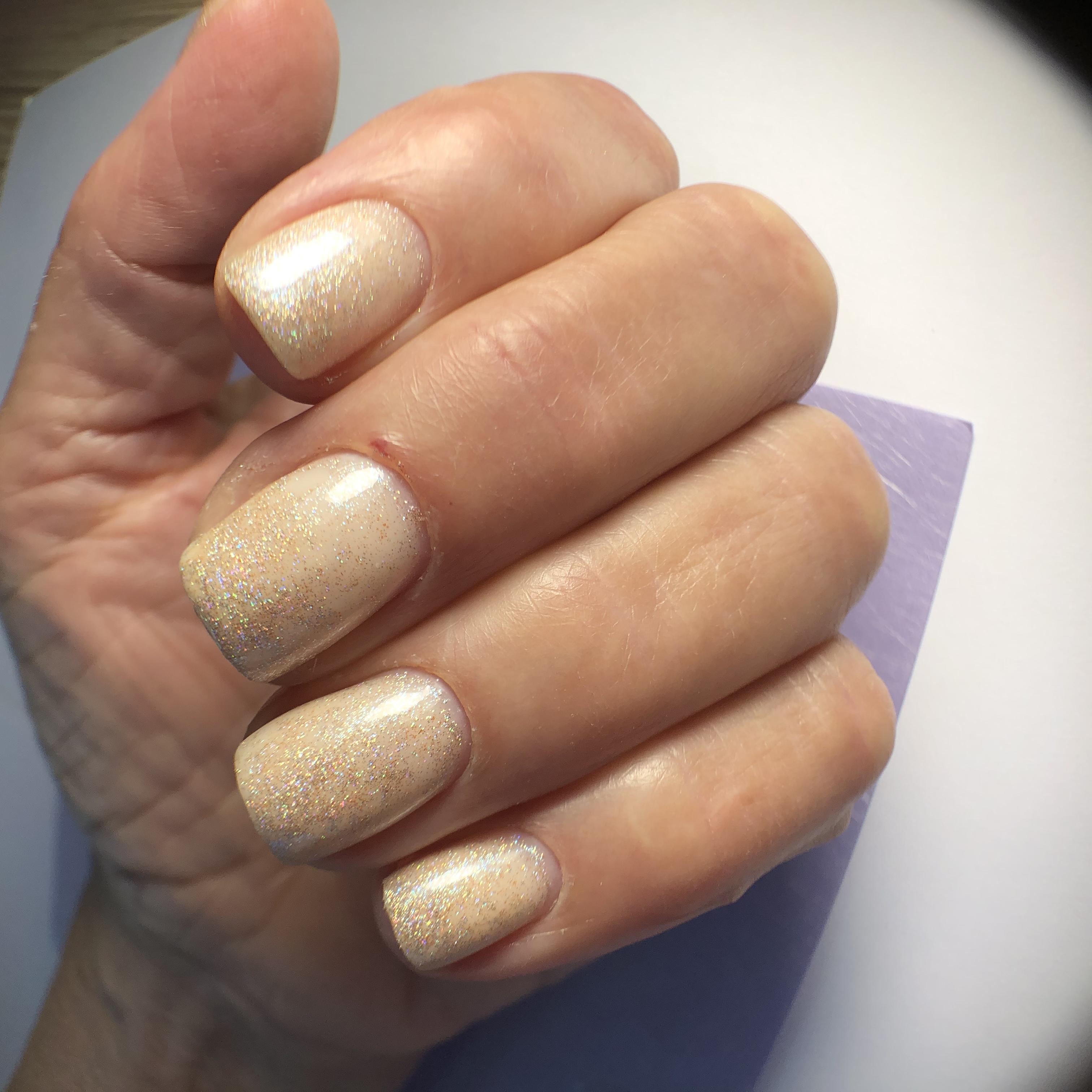 Маникюр с золотыми блестками в персиковом цвете на короткие ногти.