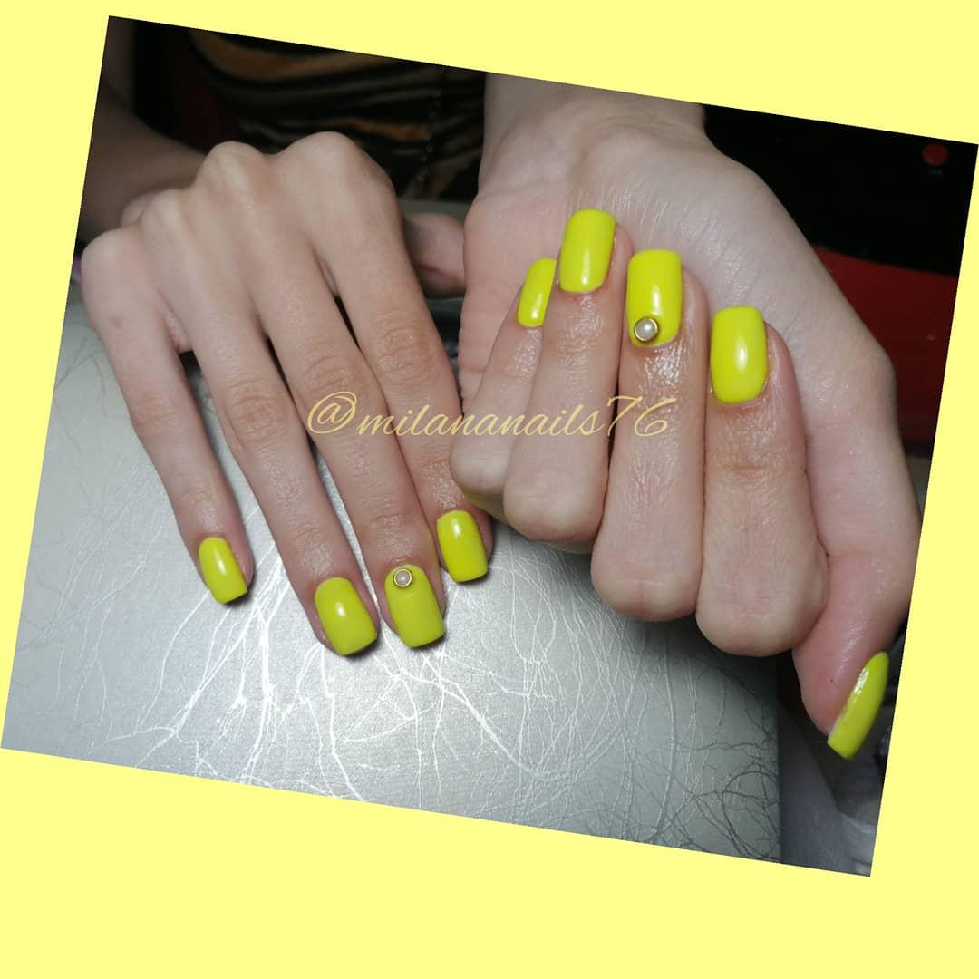 Маникюр со стразами в желтом цвете на длинные ногти.
