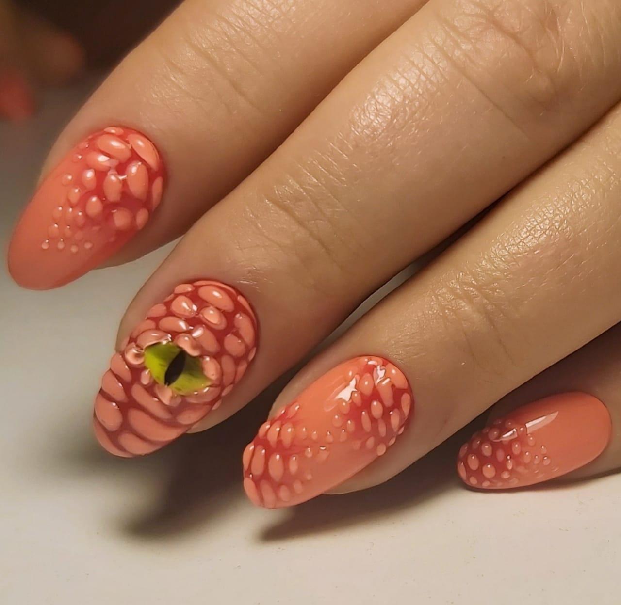 Маникюр со змеиным глазом и объемным рисунком в оранжевом цвете на короткие ногти.