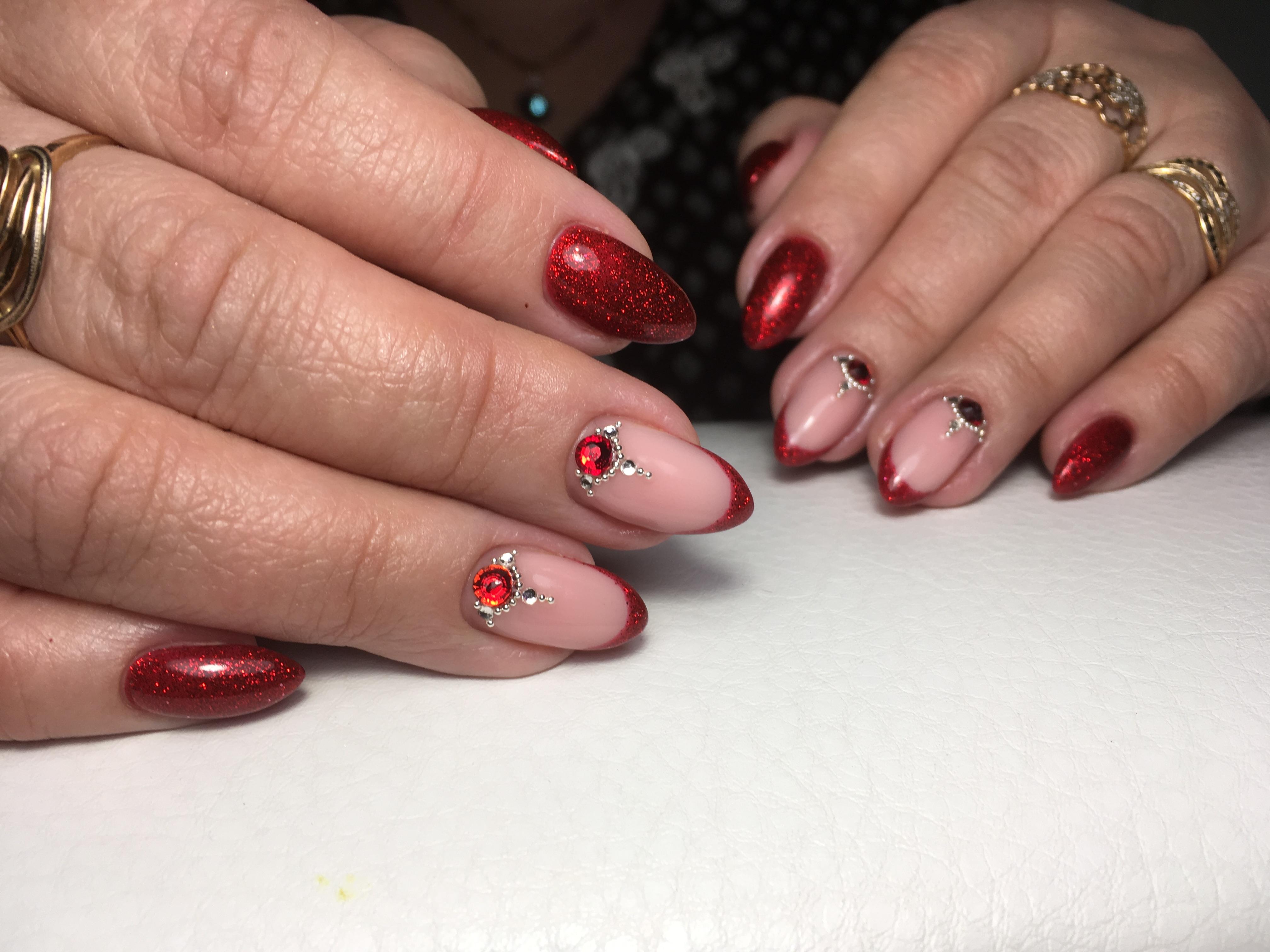 Маникюр с френч-дизайном, блестками и стразами в темно-красном цвете.