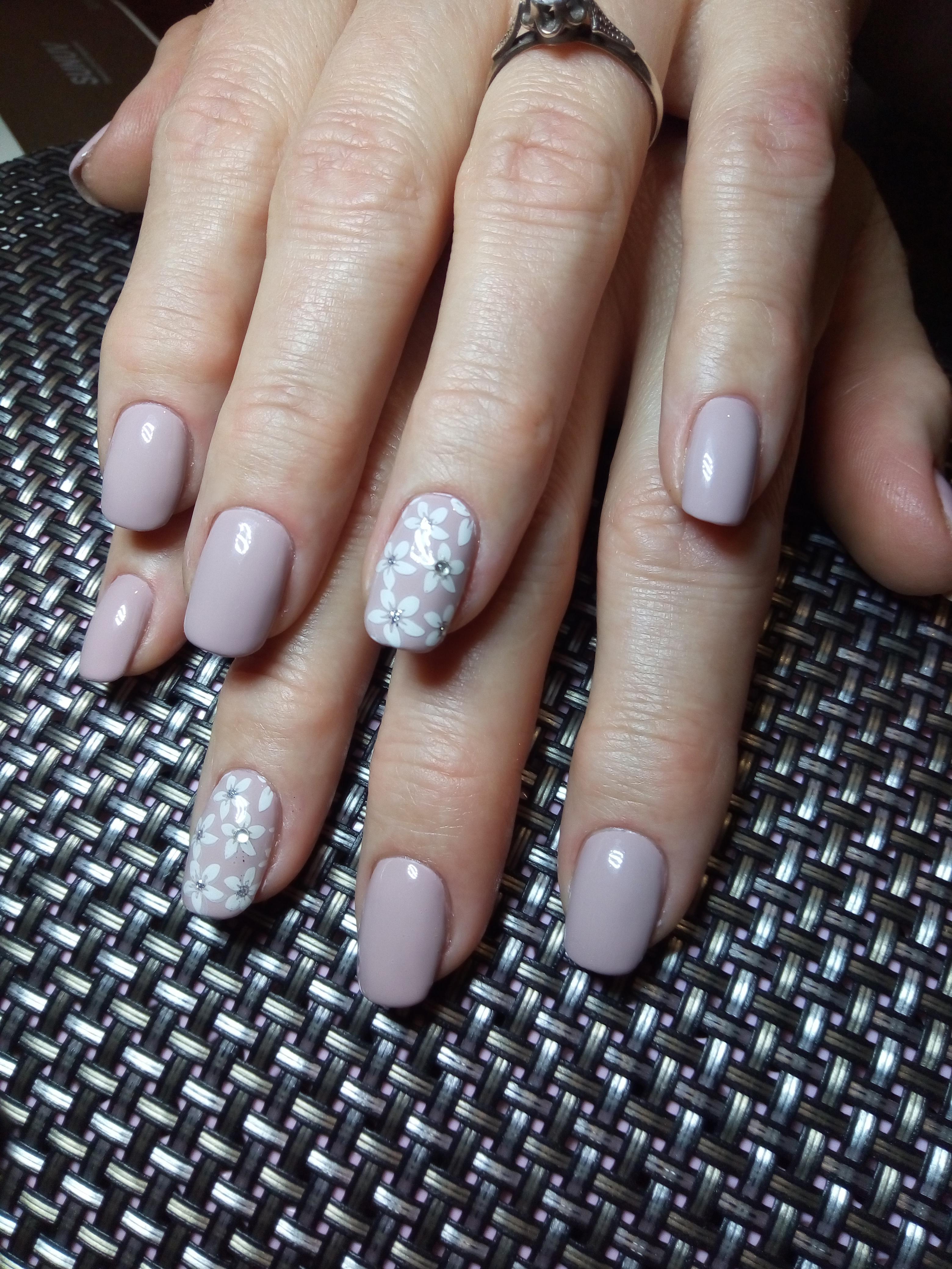Маникюр с цветочным стемпингом и стразами в пастельных тонах на короткие ногти.