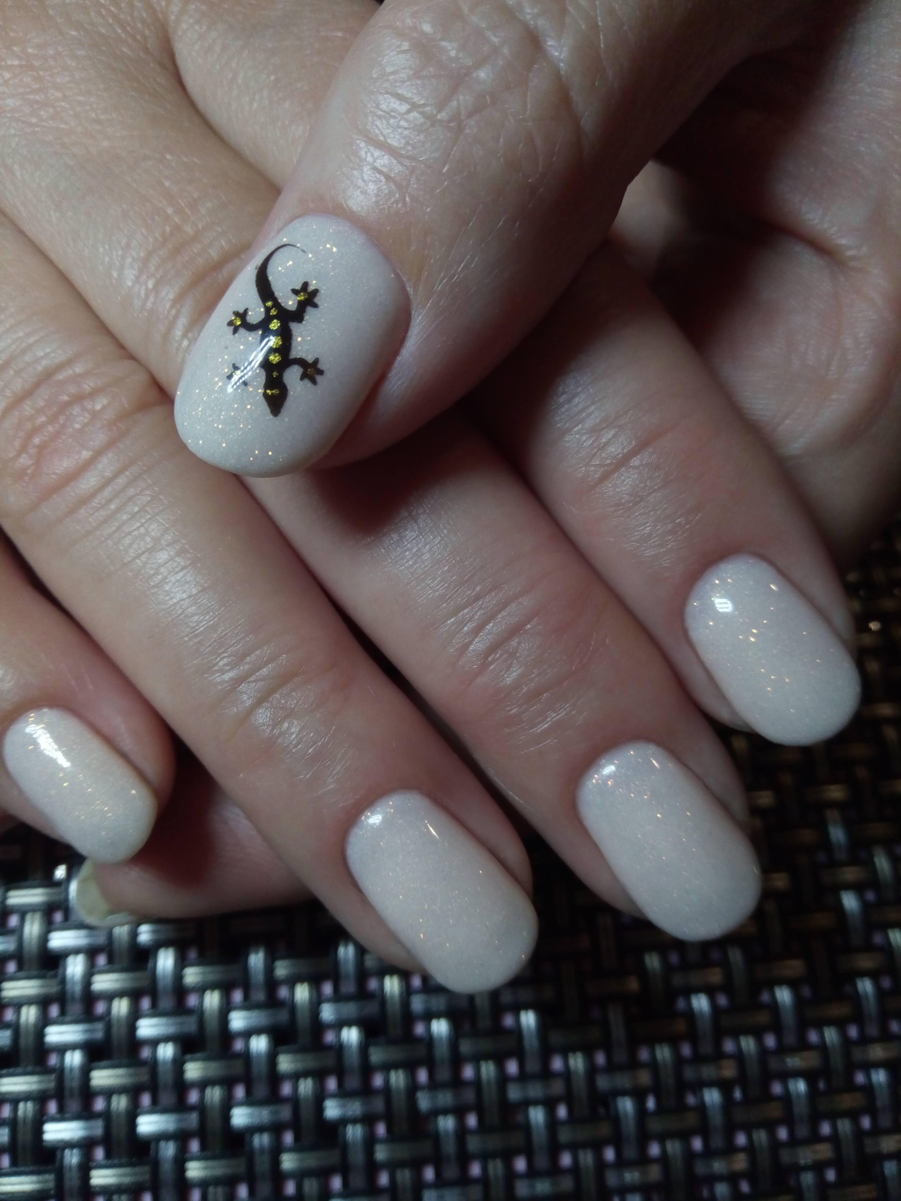 Маникюр с ящерицей и блестками в бежевом цвете на короткие ногти.