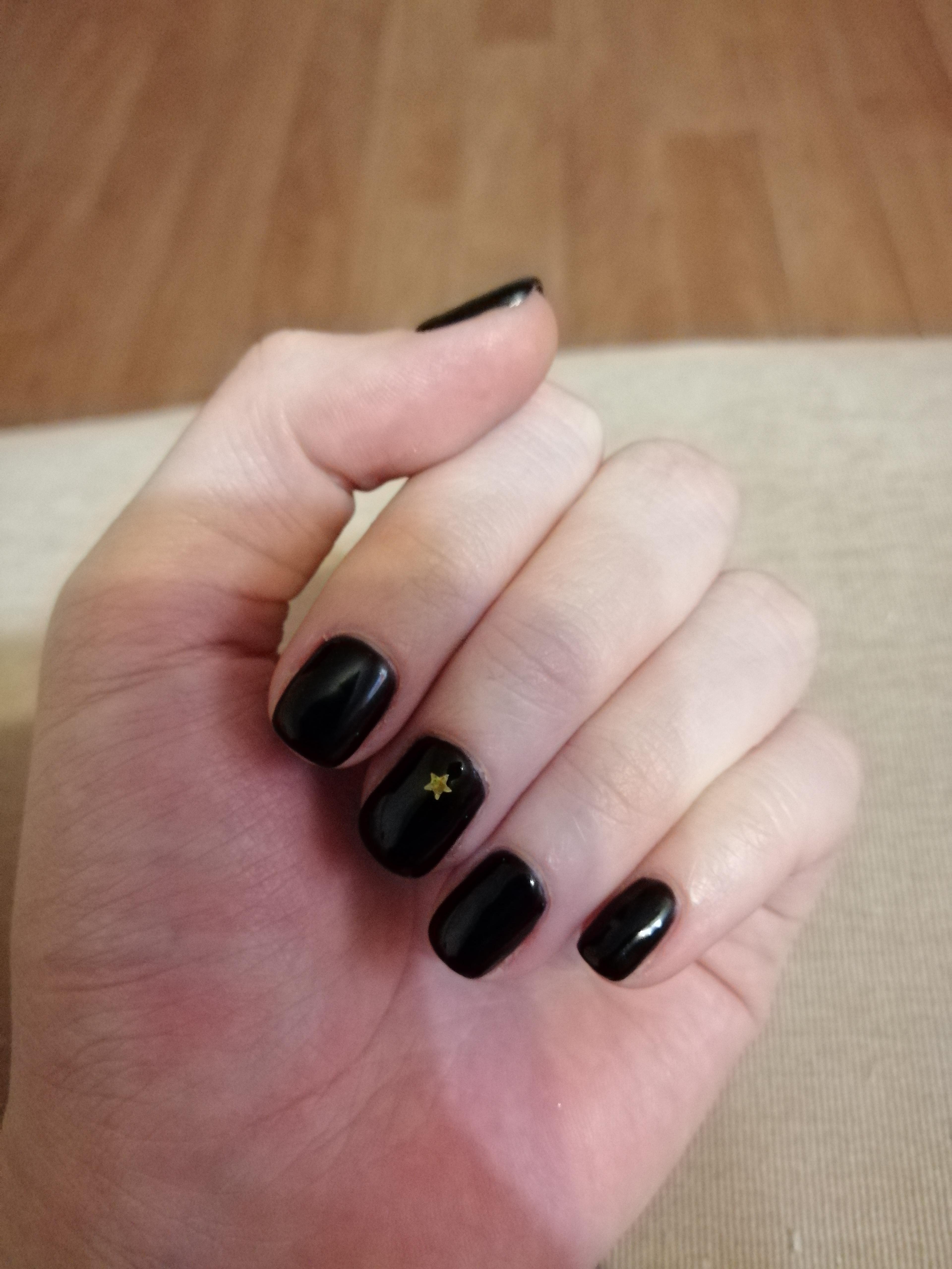 Маникюр со звездочкой в черном цвете.