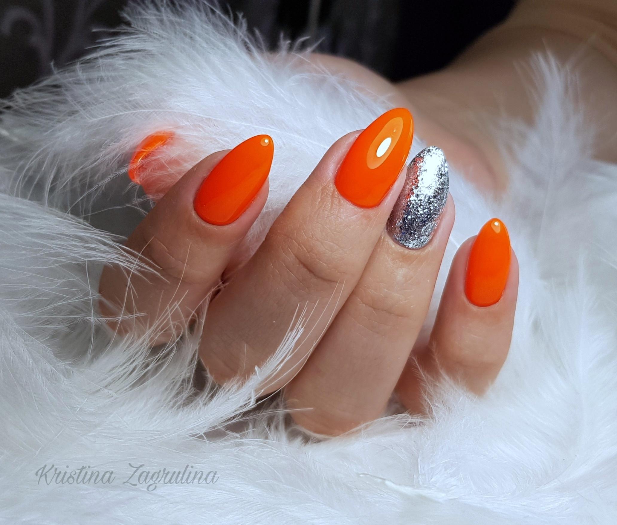Маникюр с серебряными блестками в оранжевом цвете.