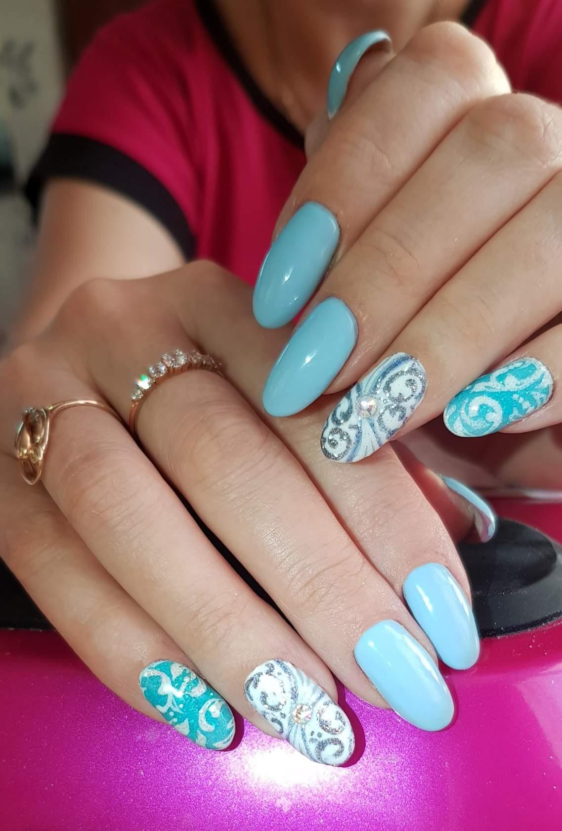 Маникюр с песочным кружевным дизайном и блестками в голубом цвете.