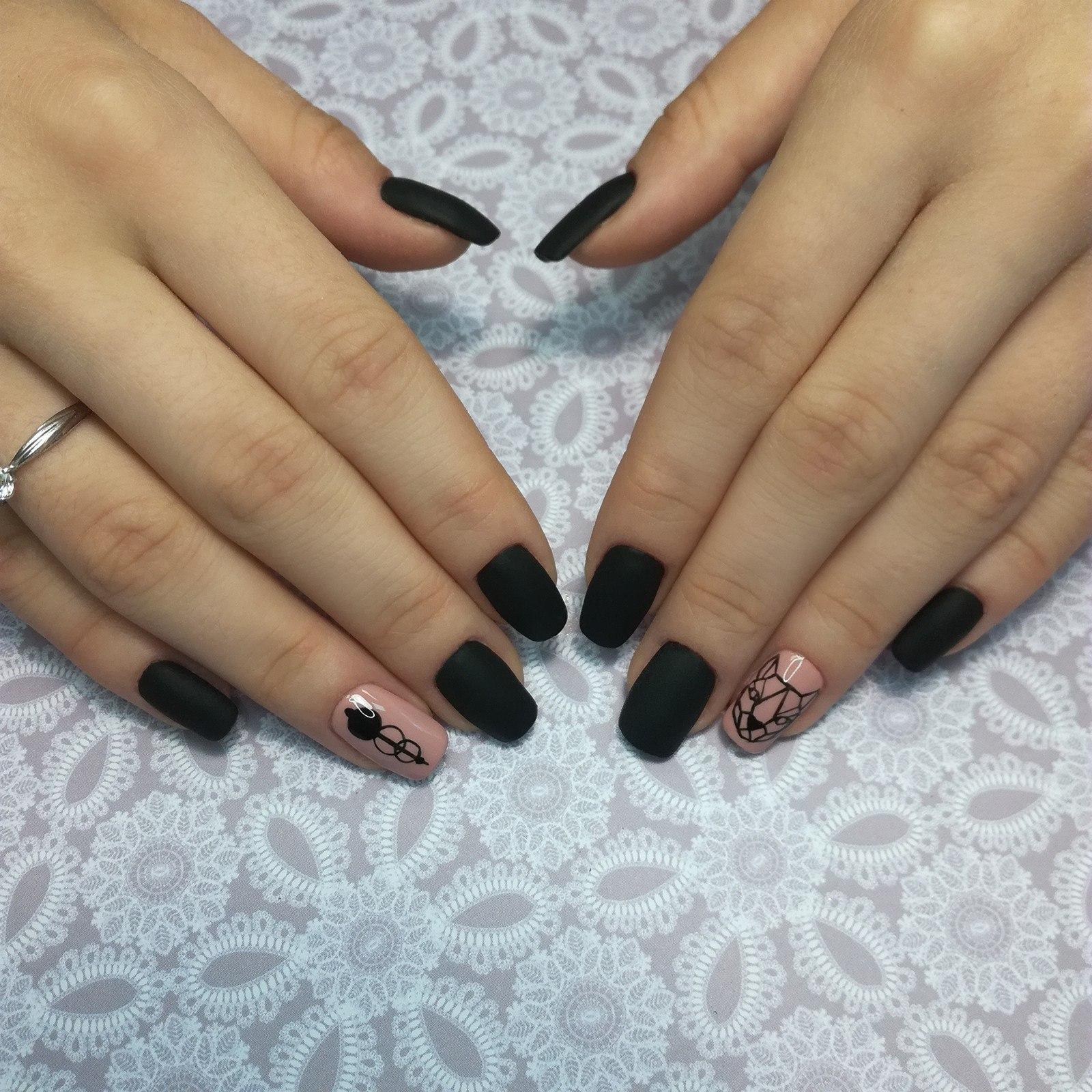 Матовый маникюр с геометрическими слайдерами в черном цвете.