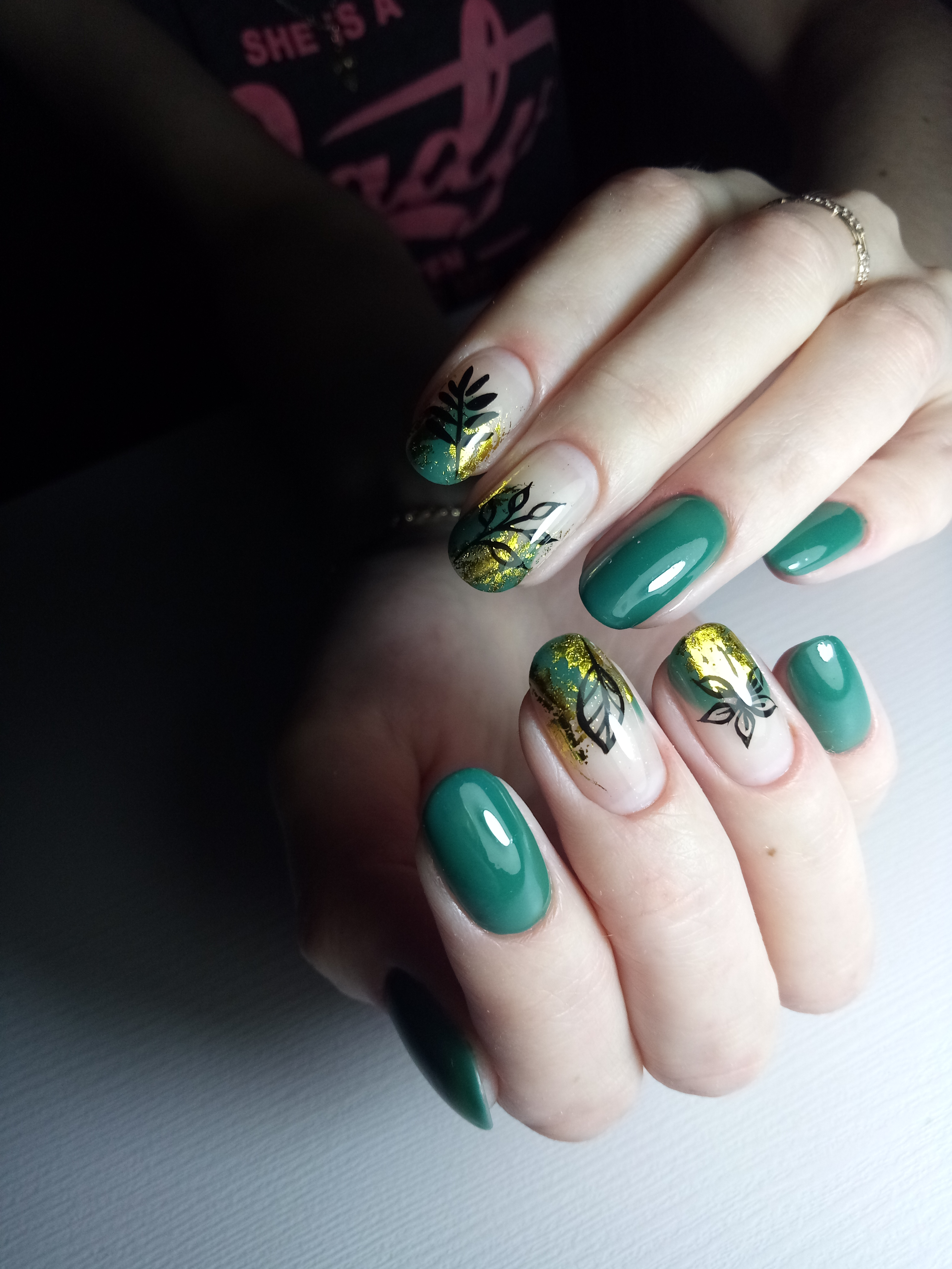 Маникюр с растительными слайдерами и золотой фольгой в зеленом цвете.