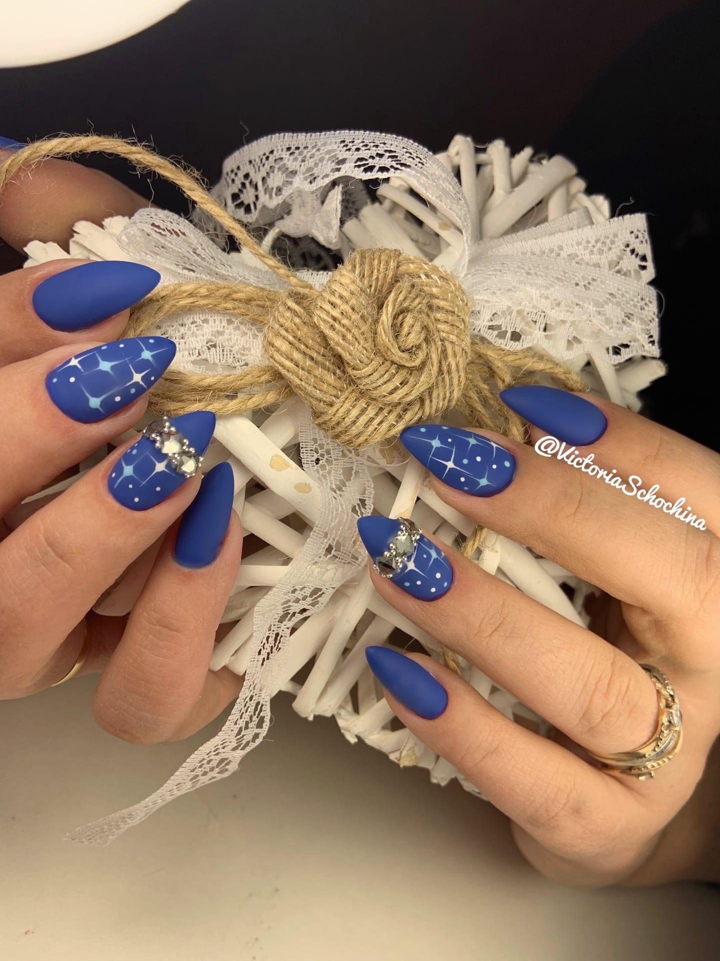 Матовый маникюр со звездочками и стразами в синем цвете.