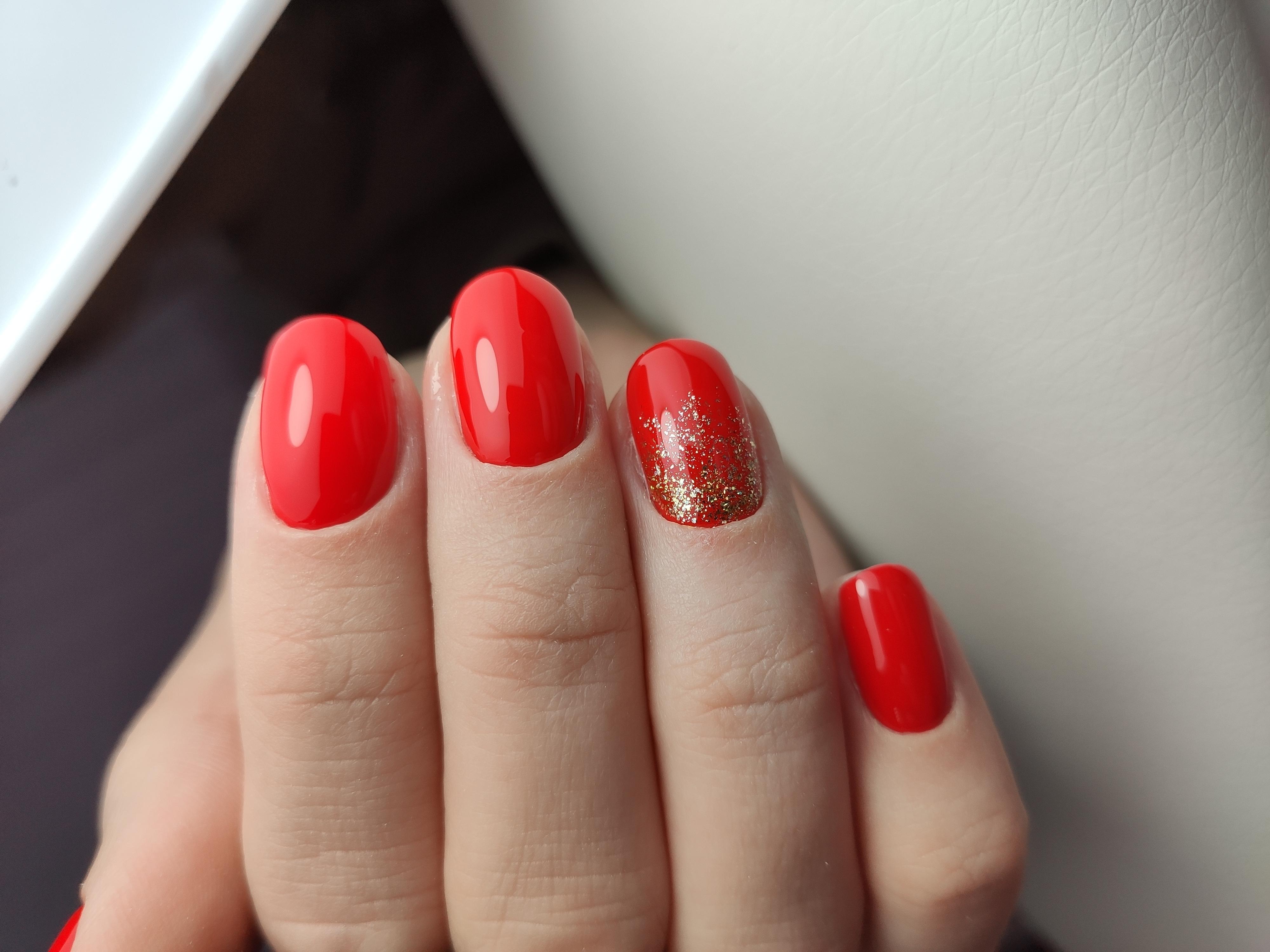 Маникюр в красном цвете с золотыми блёстками.
