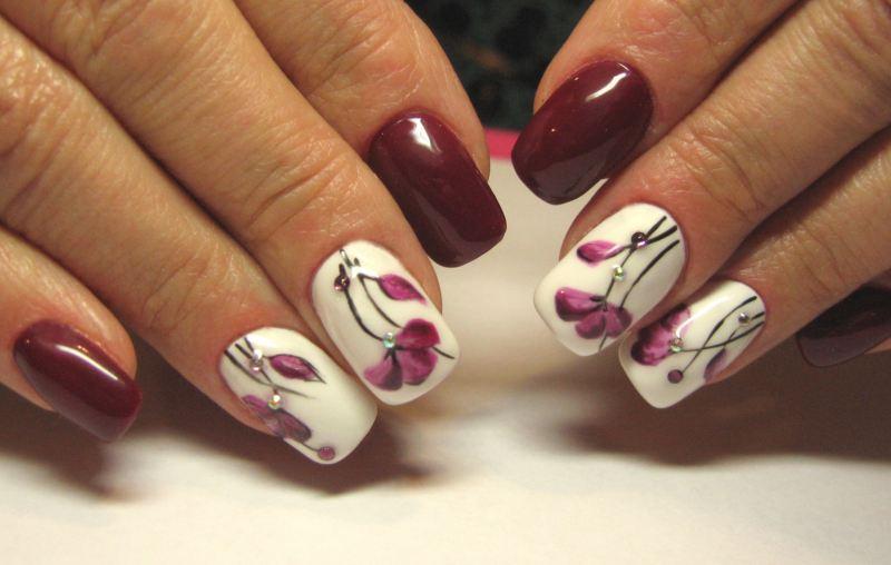 Маникюр с цветочным рисунком в баклажановом цвете на короткие ногти.
