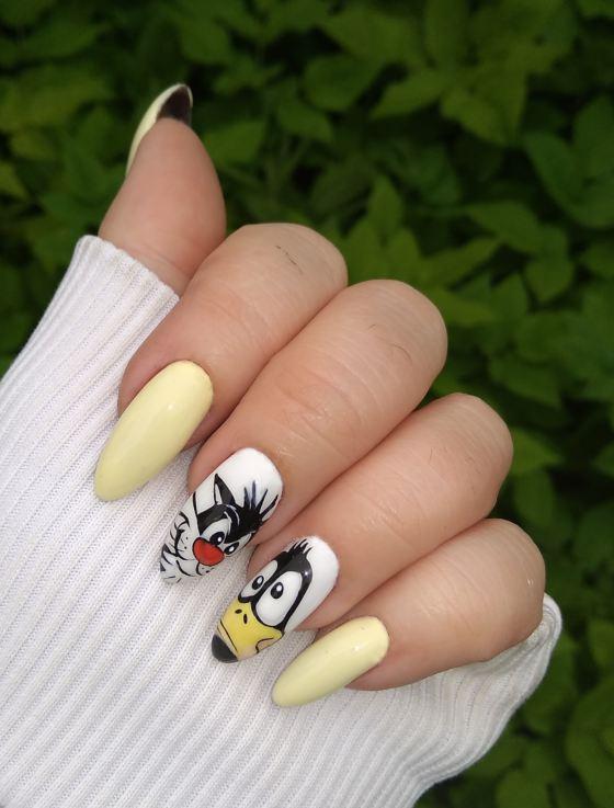 Маникюр с мультяшным рисунком в желтом цвете на длинные ногти.