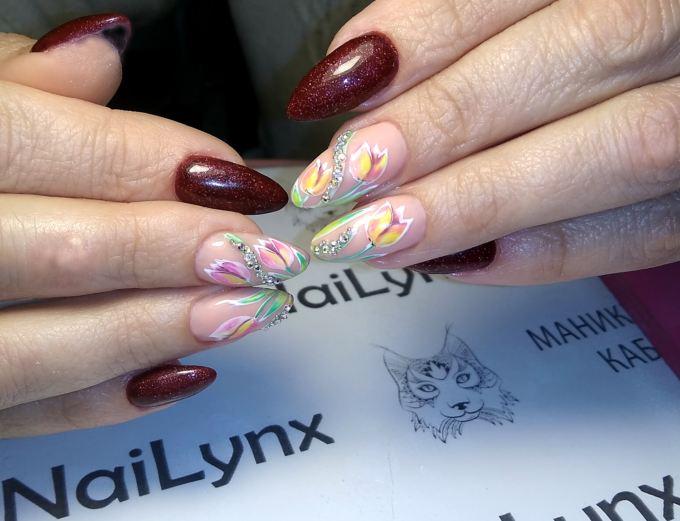 Маникюр с цветочным рисунком и стразами в темно-красном цвете на длинные ногти.