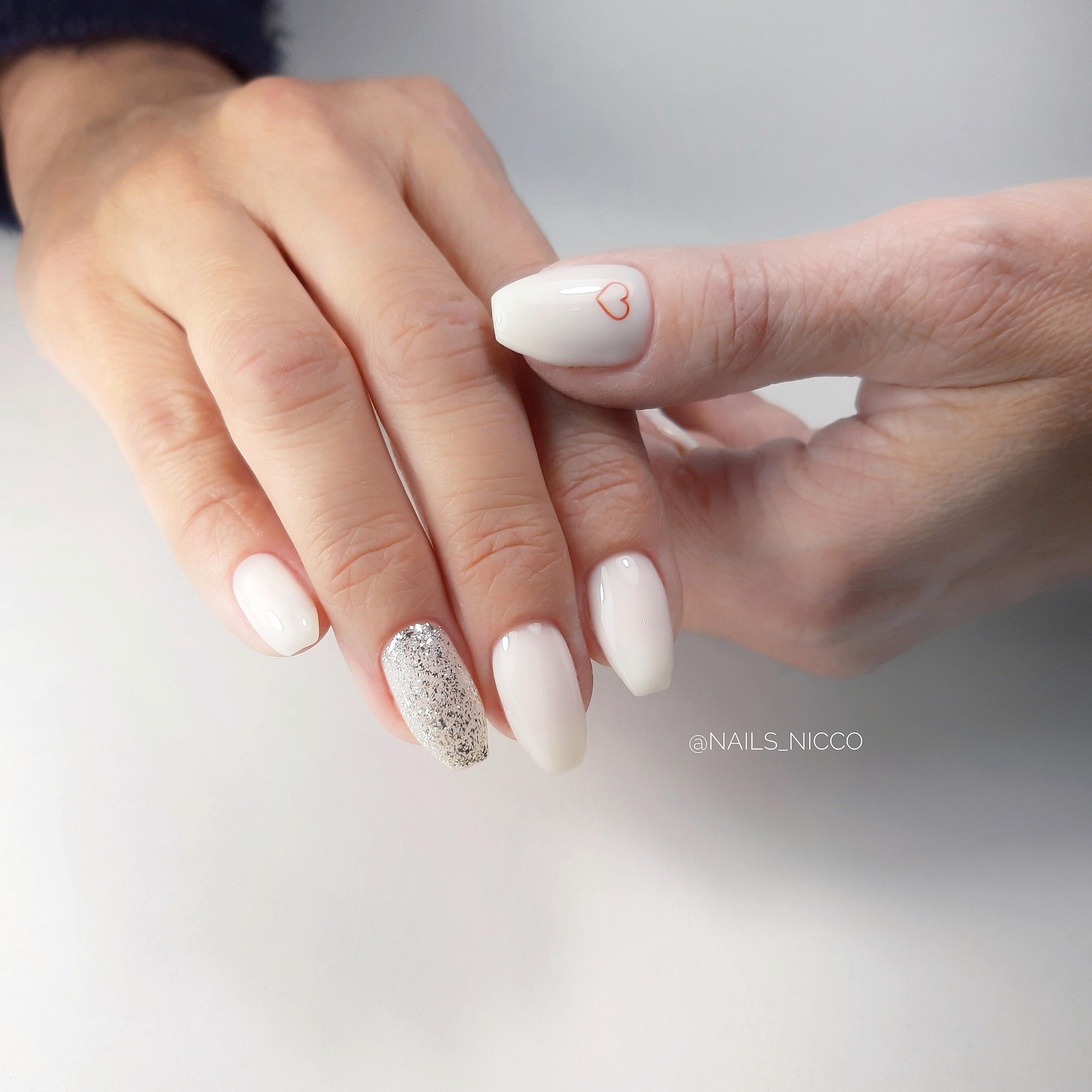 Маникюр с серебряными блестками в молочном цвете на длинные ногти.