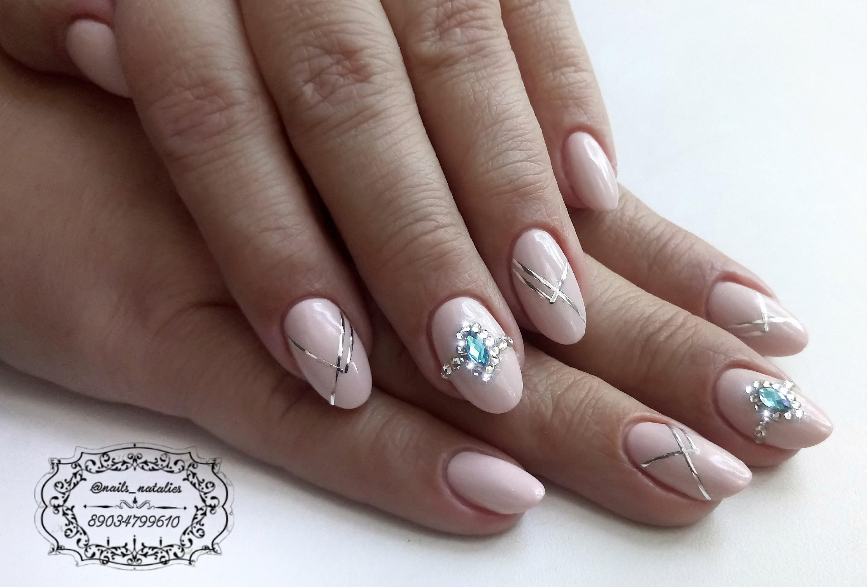 Маникюр в нежном розовом цвете с серебряным полосками и цветными стразами.