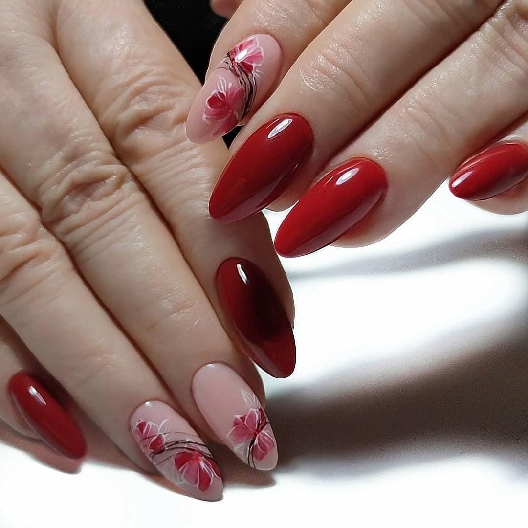 Маникюр с цветочным рисунком в бордовом цвете на длинные ногти.