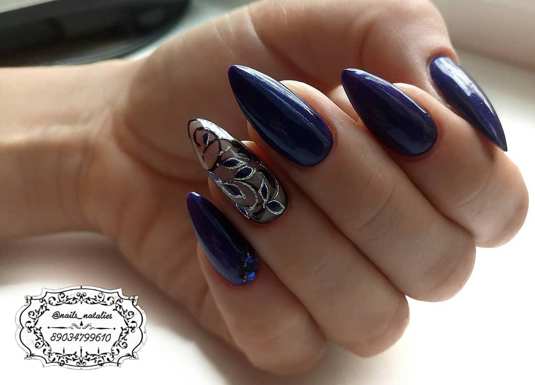 Маникюр в синем цвете с растительными вензелями и серебряными блёстками.