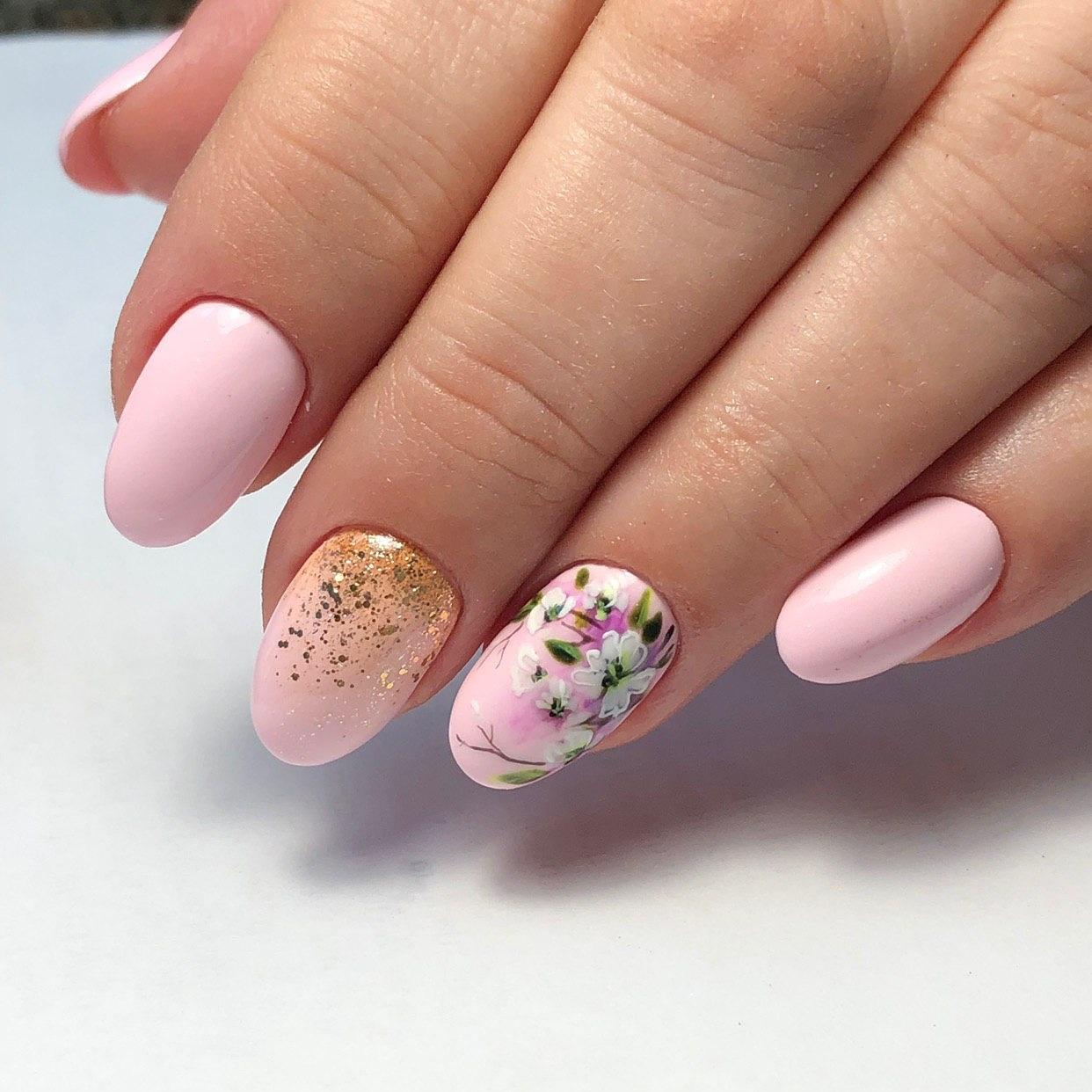 Маникюр с цветочным рисунком и золотыми блестками в розовом цвете.