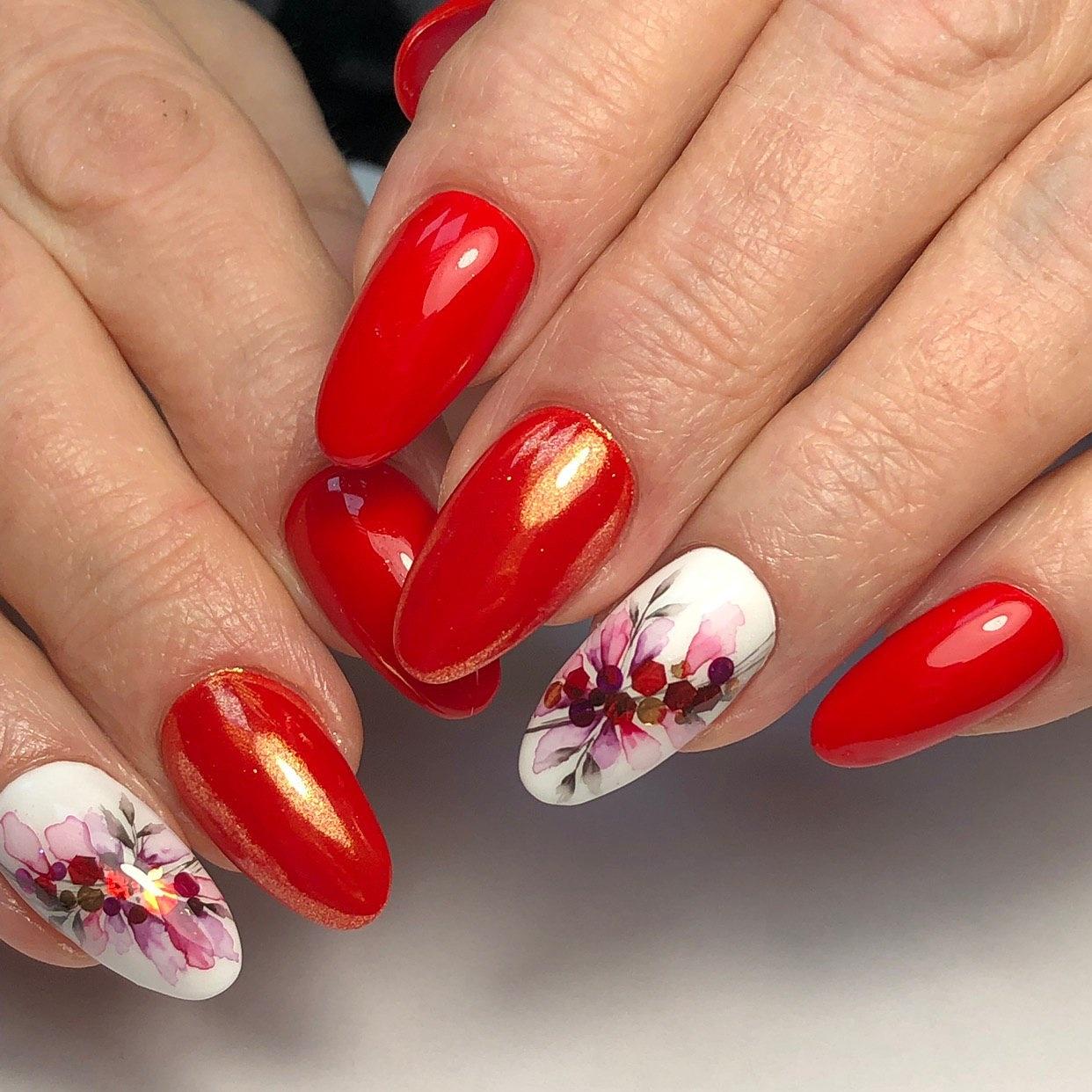 Маникюр с акварельным цветочным рисунком в красном цвете.