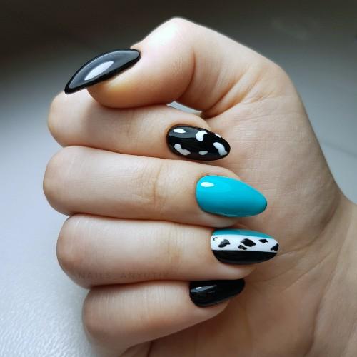Маникюр в чёрном цвете с голубым дизайном и контрастным абстрактным рисунком.