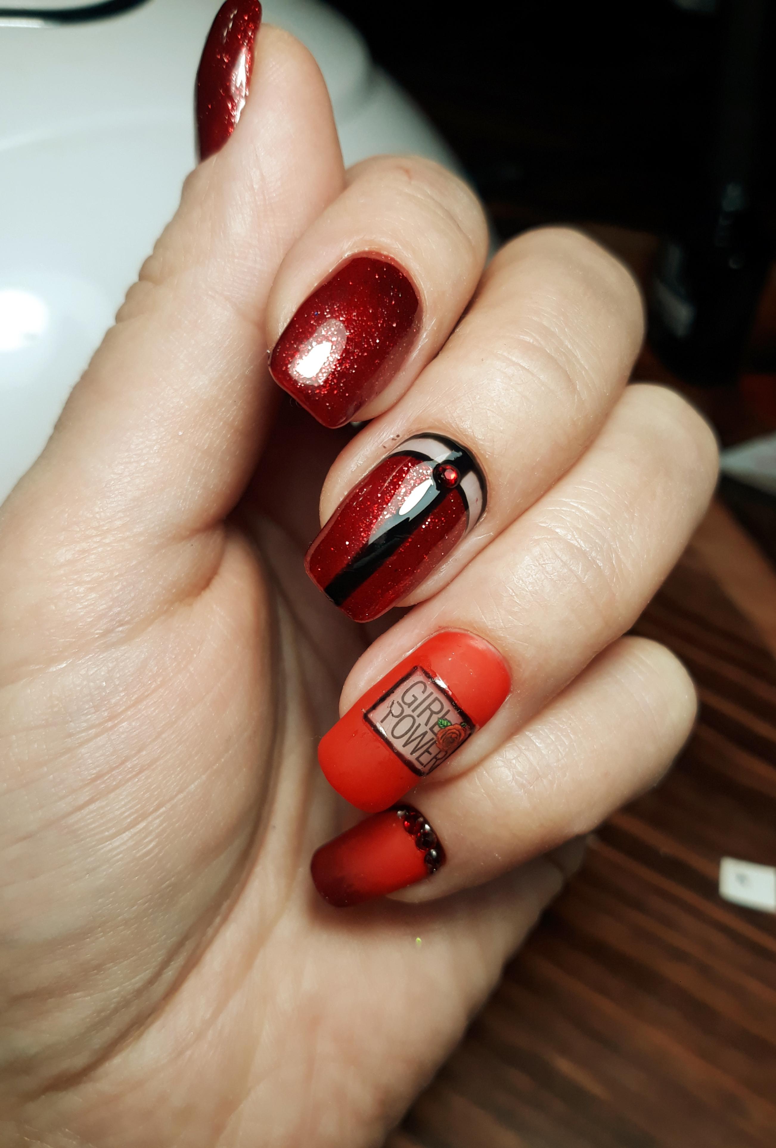 Геометрический маникюр с надписями, блестками и стразами в темно-красном цвете.