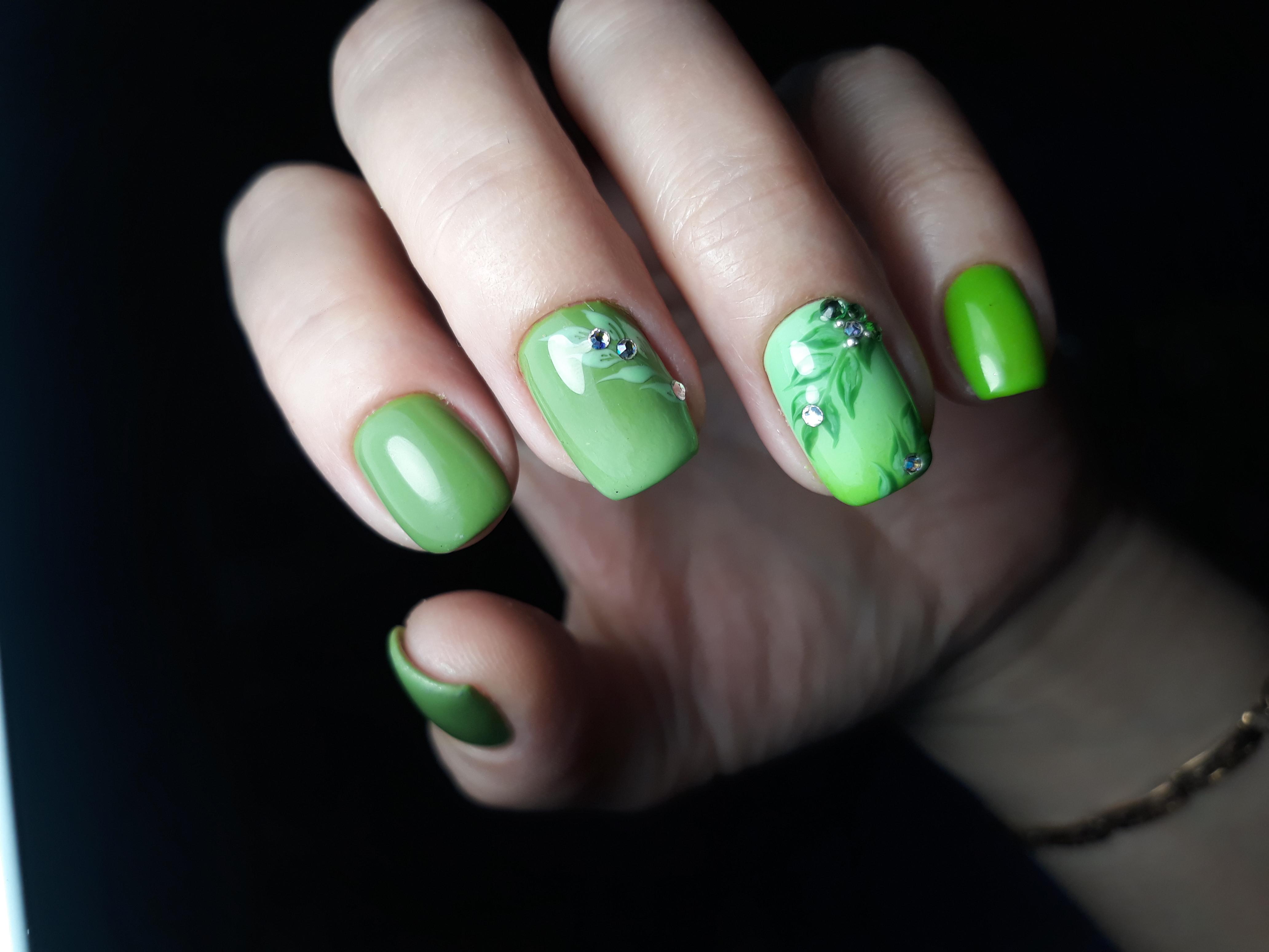 Маникюр с растительным рисунком и стразами в зеленом цвете.