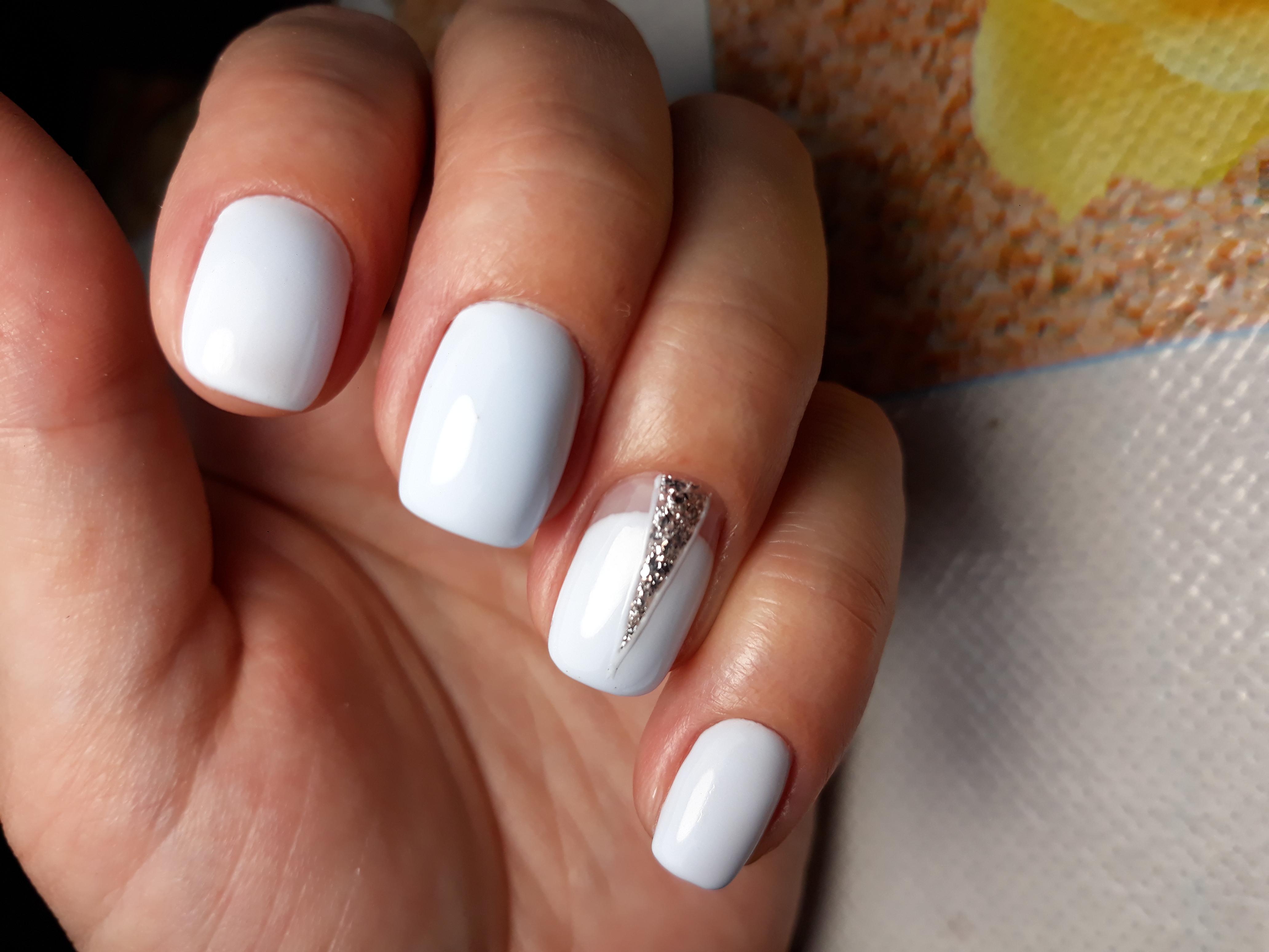 Маникюр с серебряными блестками в белом цвете.