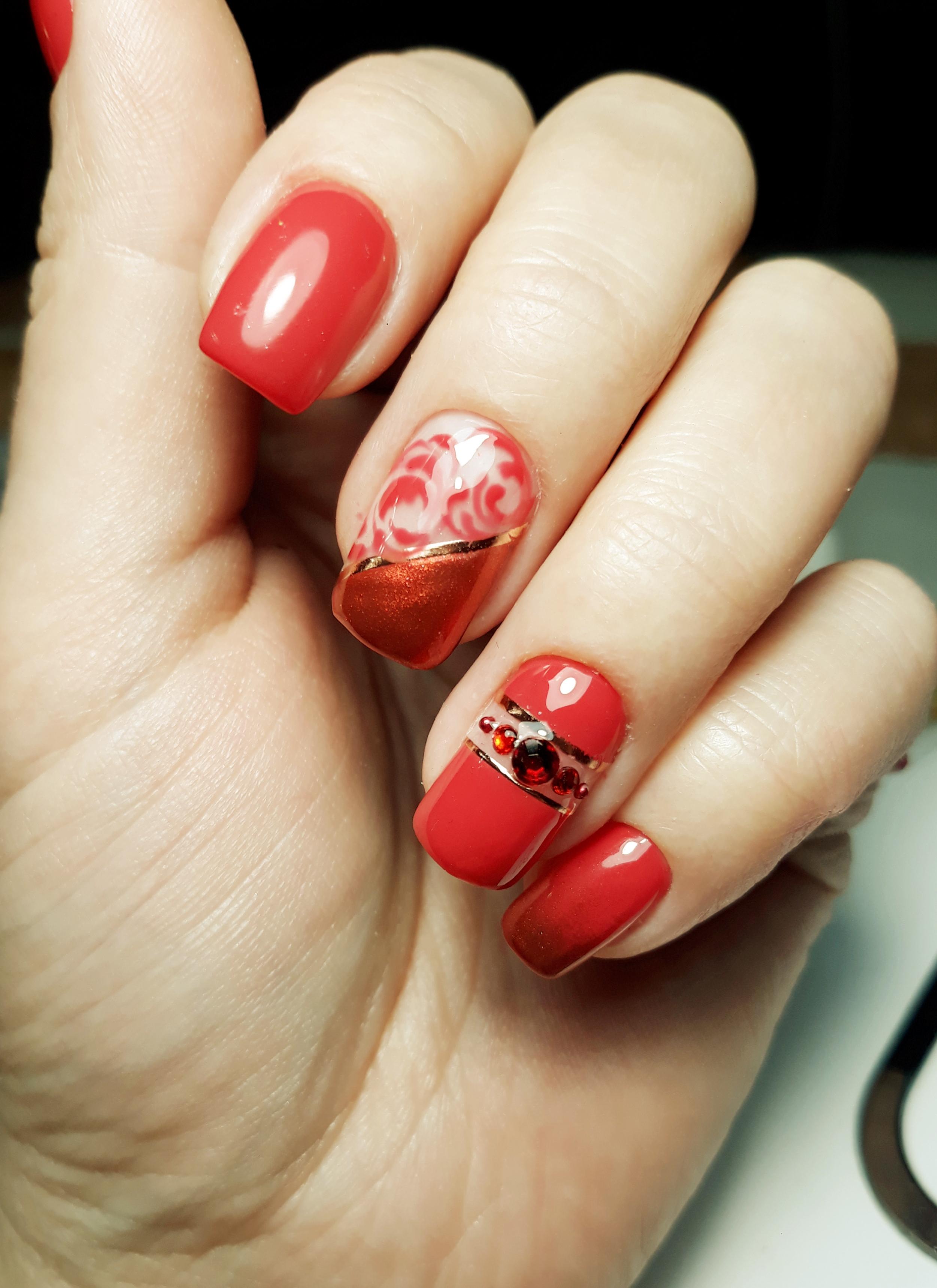 Маникюр с золотыми полосками и стразами в красном цвете.