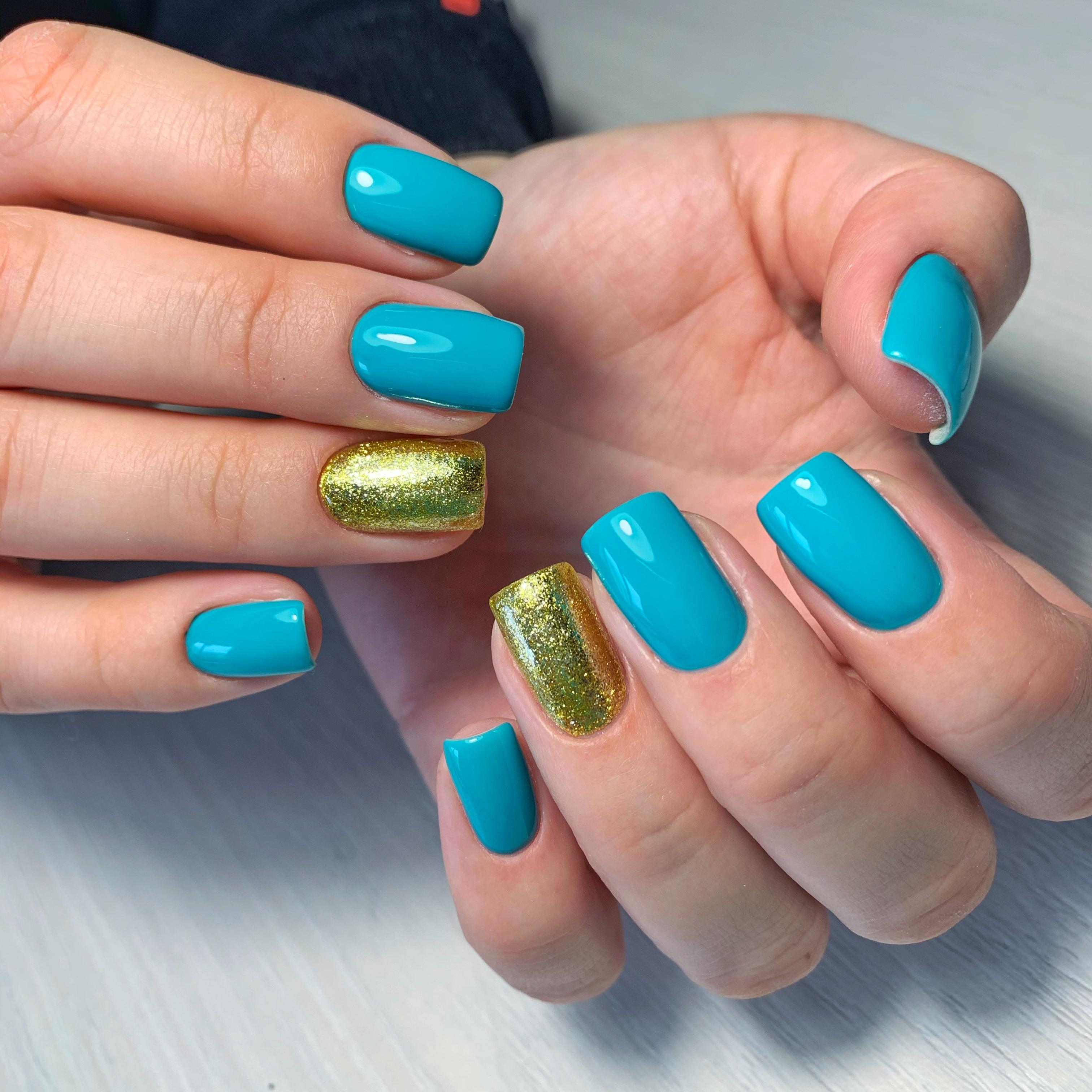 Маникюр с золотыми блестками в голубом цвете на короткие ногти.