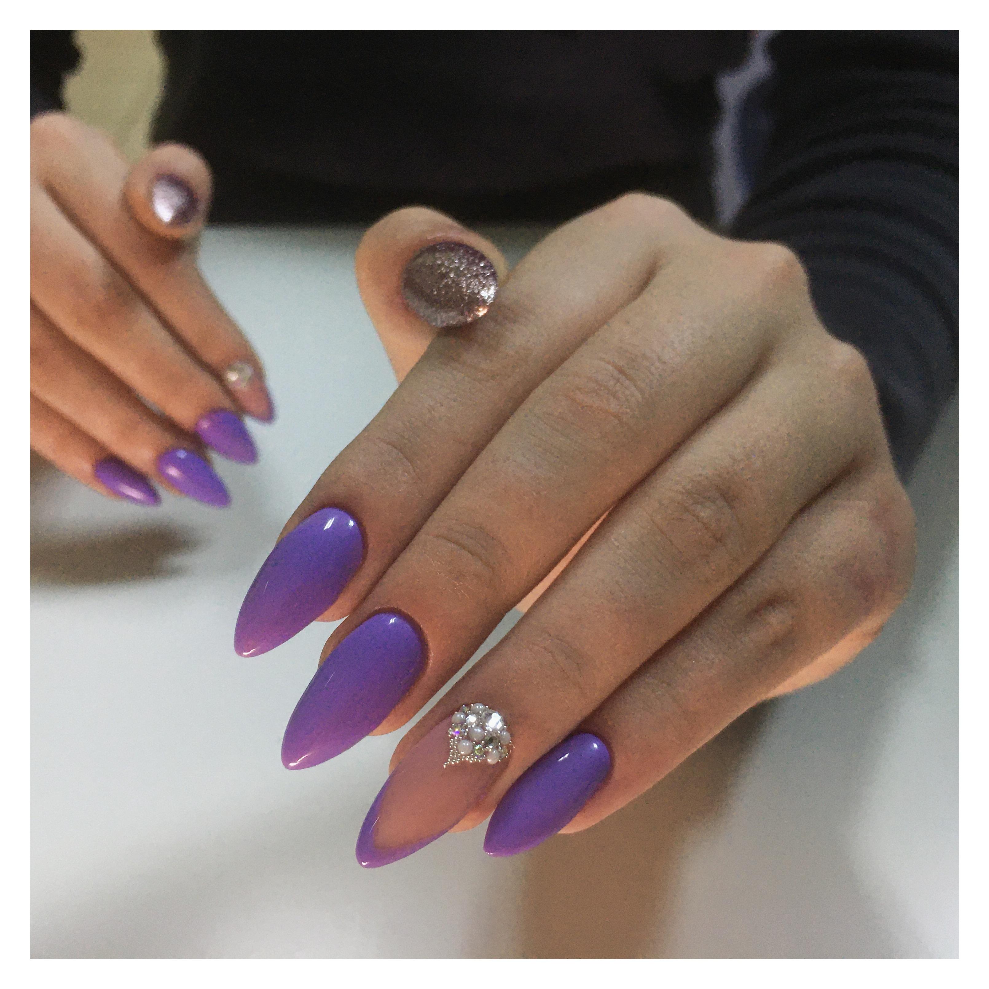 Маникюр с золотыми блестками и стразами в фиолетовом цвете.