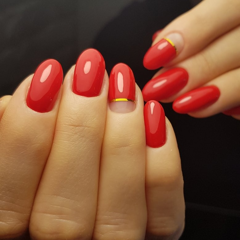 Маникюр с золотыми полосками в красном цвете.