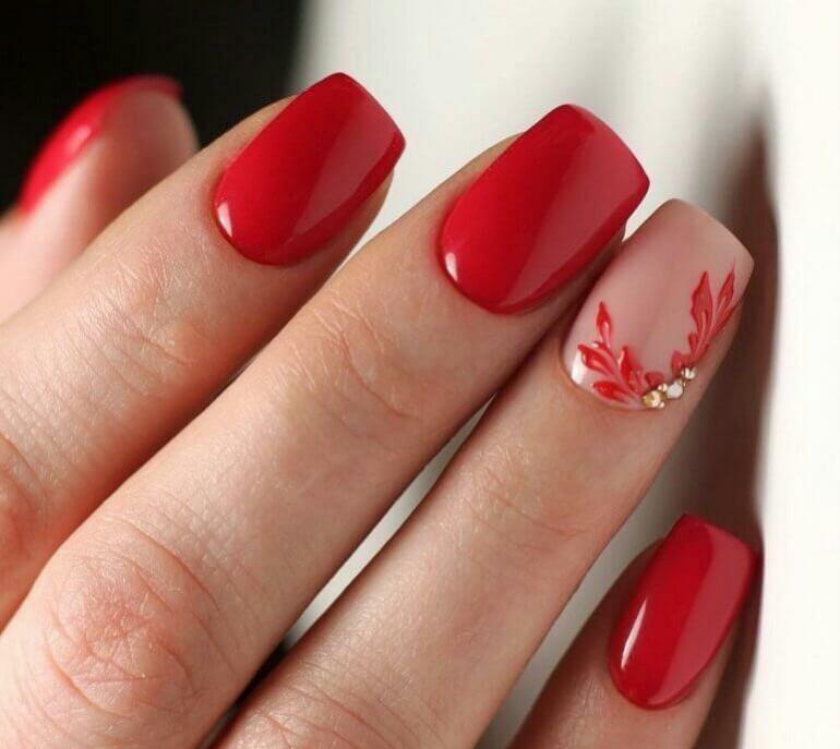 Маникюр с растительным рисунком и стразами в красном цвете.