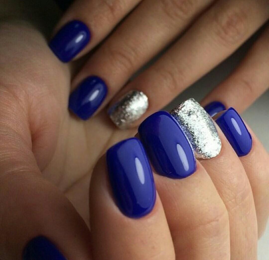 Маникюр с серебряным блестками в синем цвете.