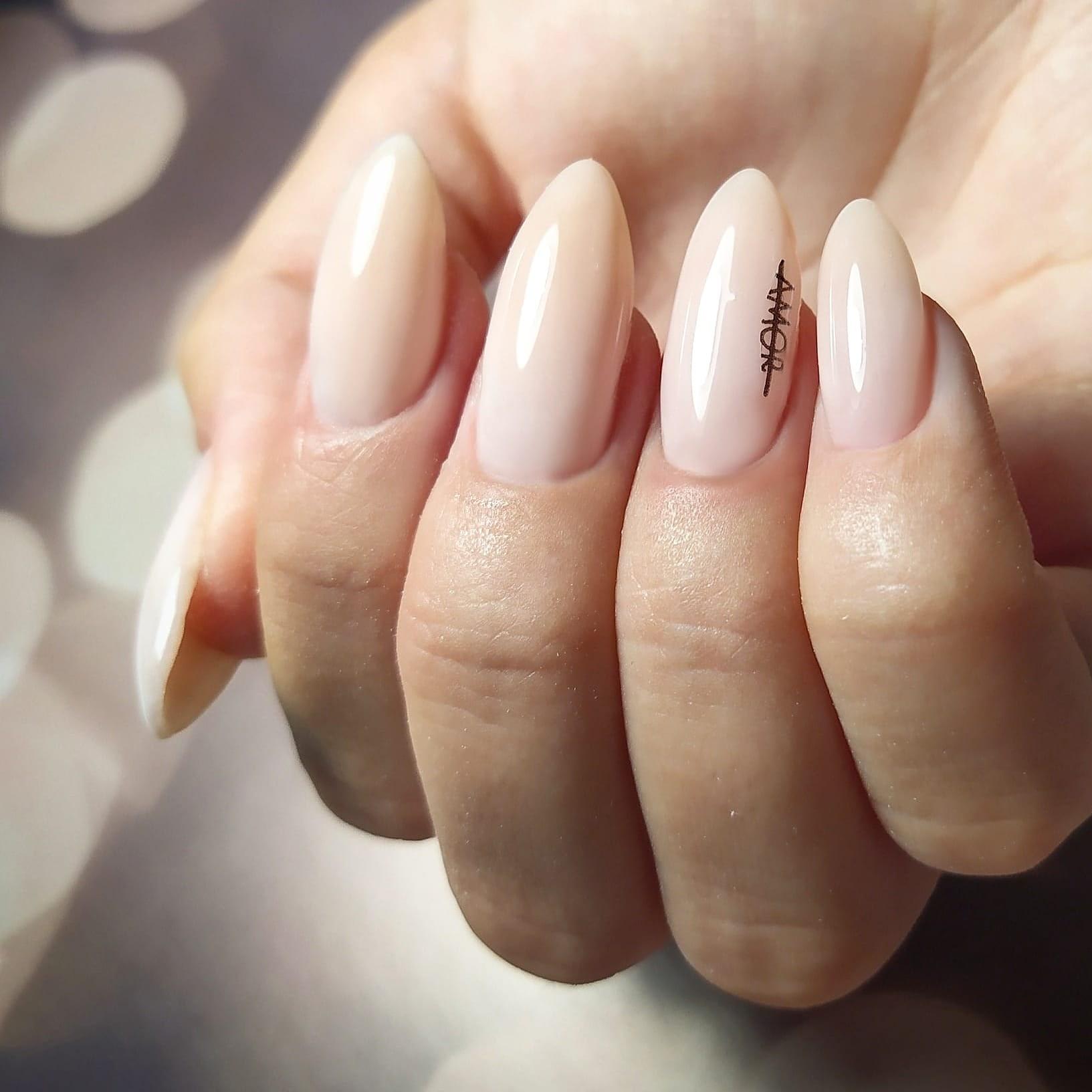 Маникюр с надписями в молочном цвете на длинные ногти.