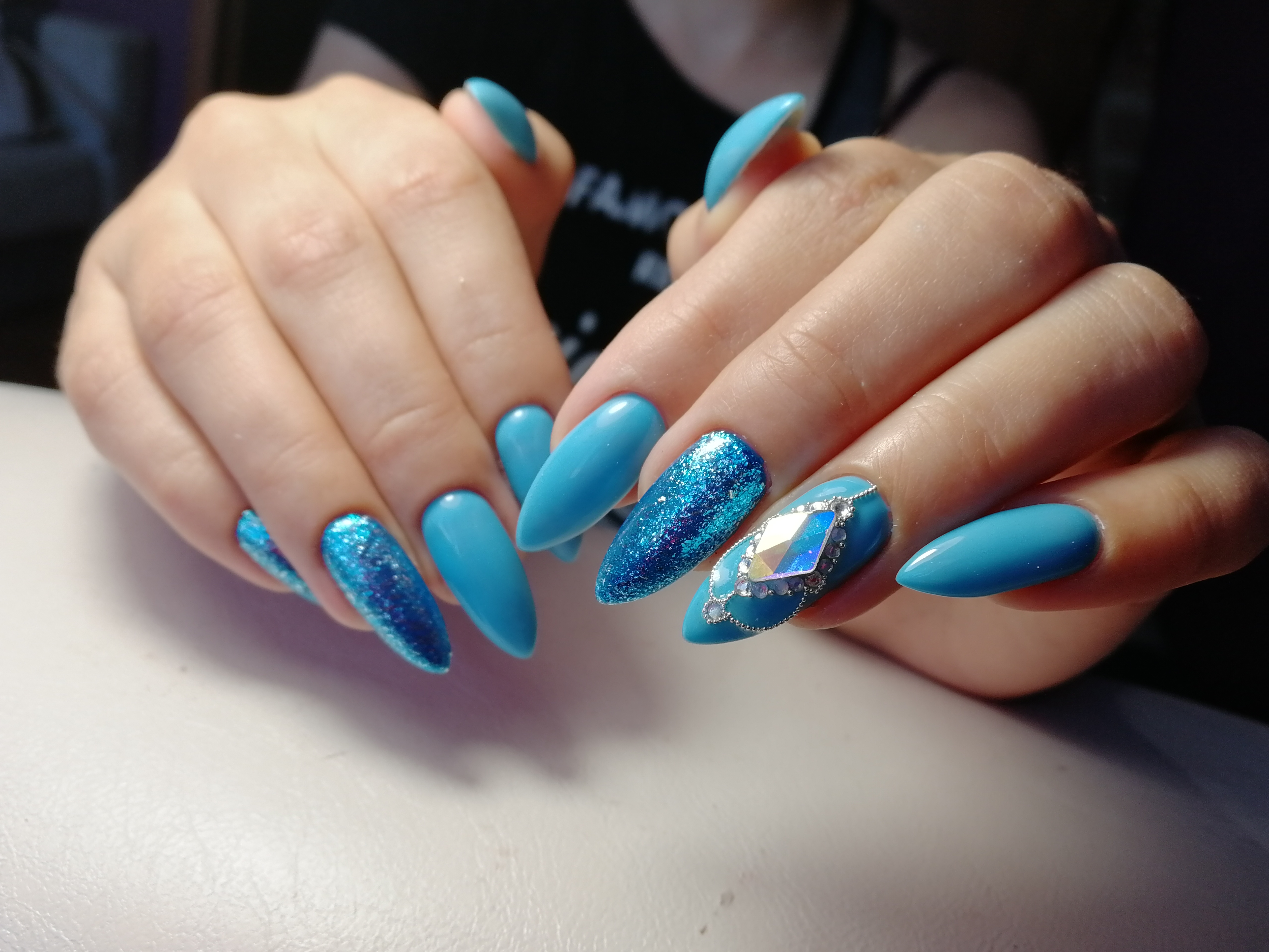 Маникюр с блестками и стразами в голубом цвете на длинные ногти.