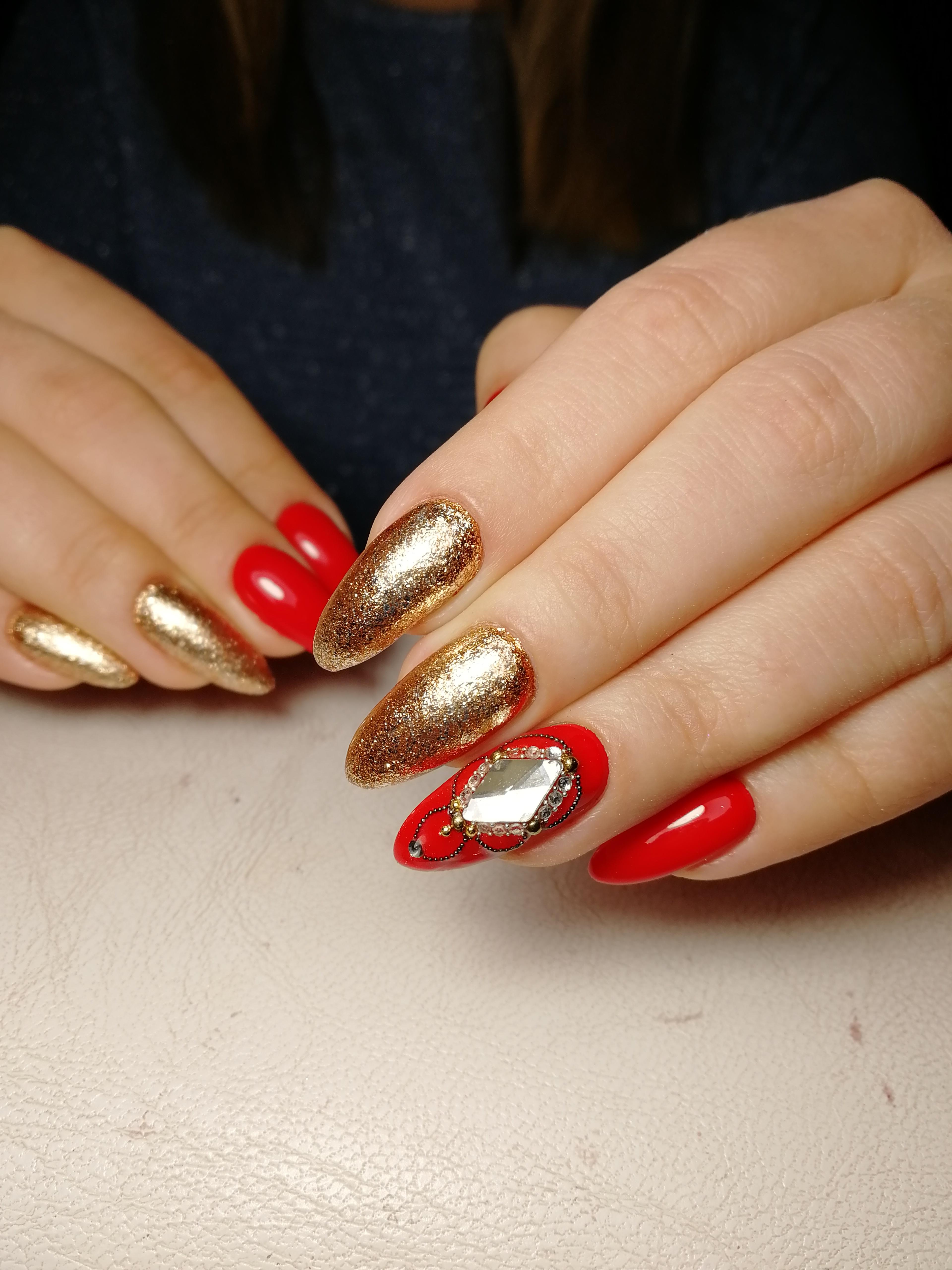 Маникюр с золотыми блестками и стразами в красном цвете.
