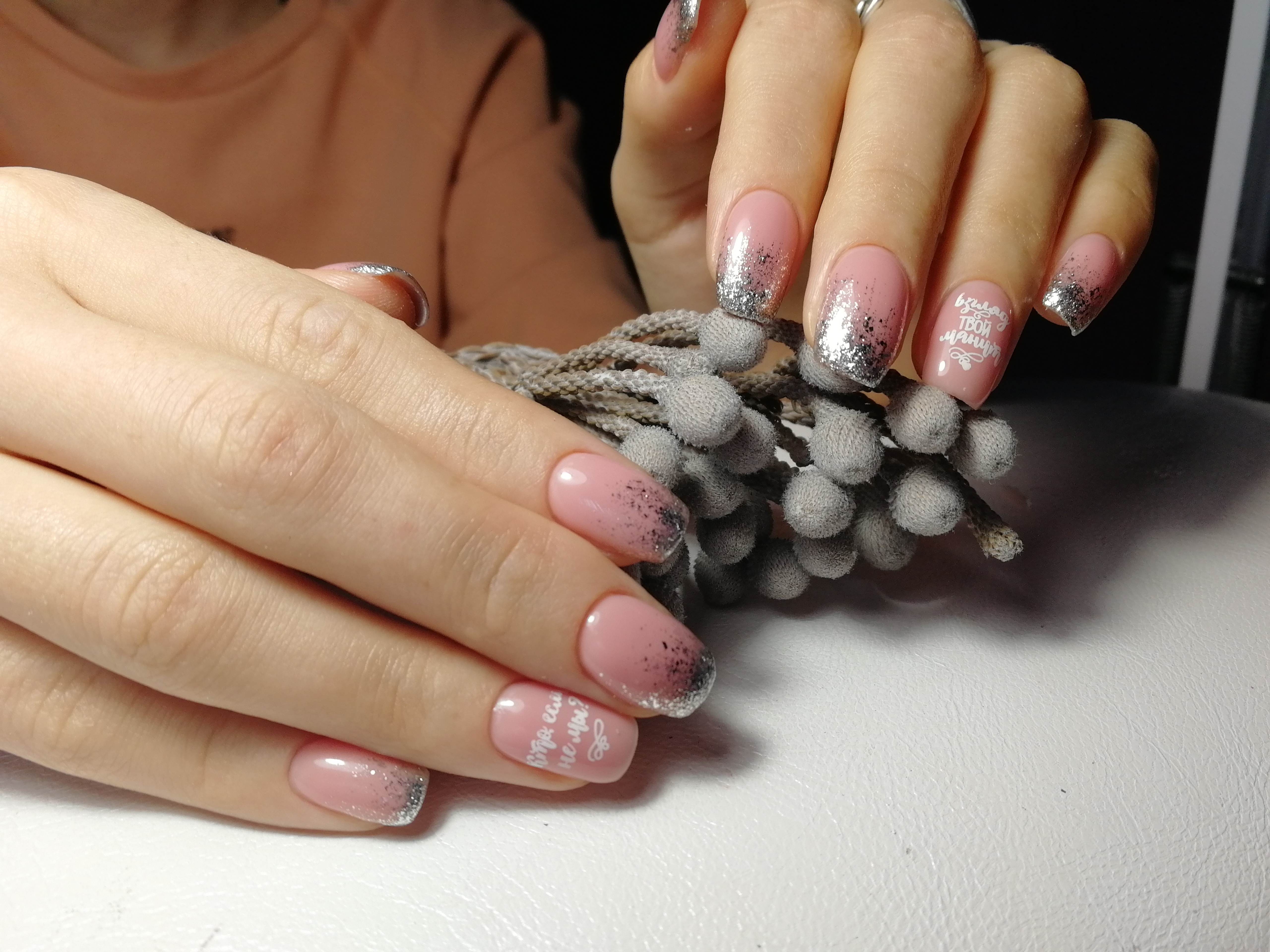 Маникюр с серебряными блестками и надписями в розовом цвете.