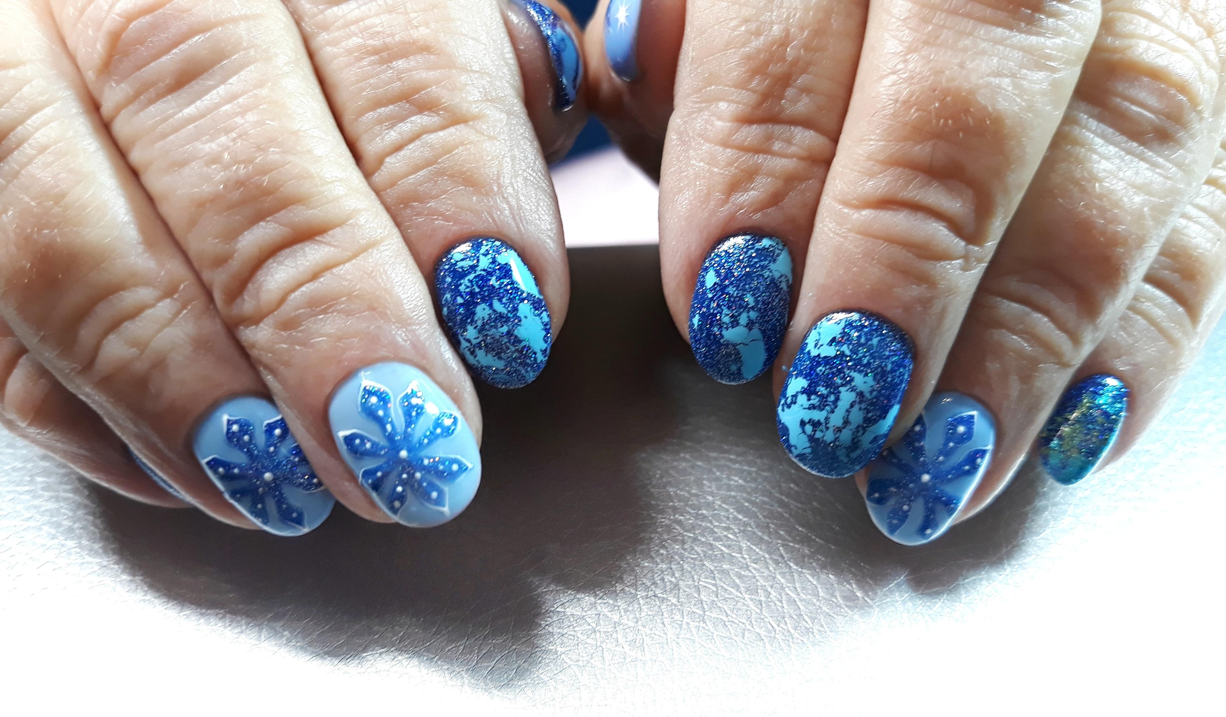 Зимний маникюр с цветной фольгой и снежинками в голубом цвете на короткие ногти.