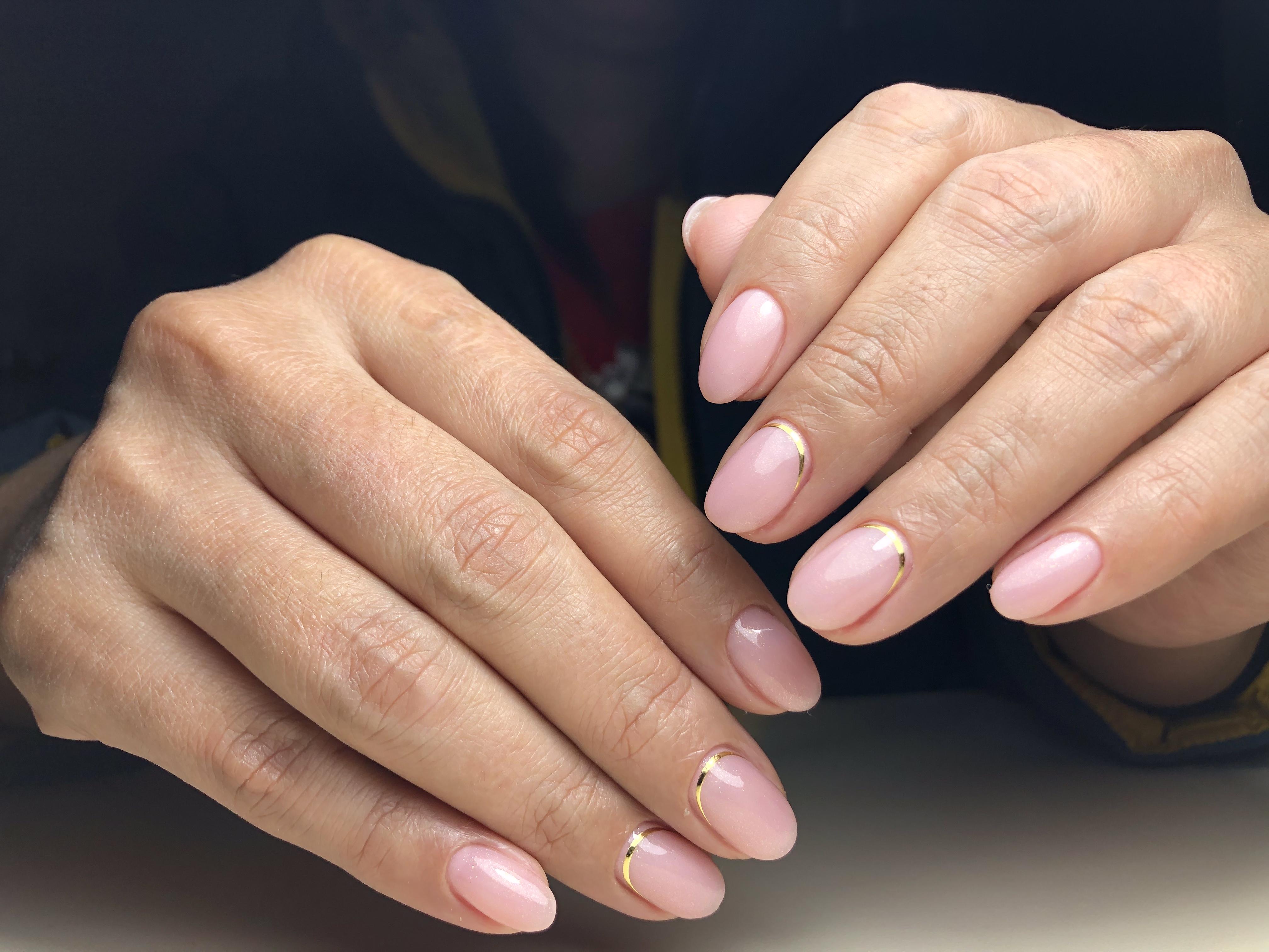Маникюр с золотыми полосками в розовом цвете.