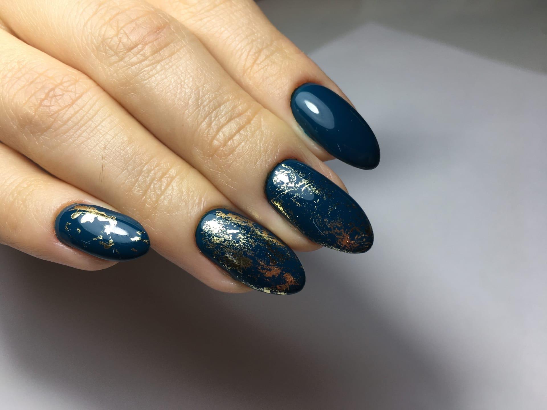 Маникюр с золотой фольгой в темно-синем цвете.