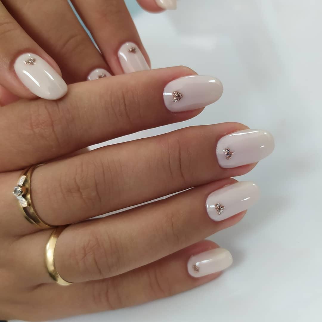Маникюр с золотыми блестками в молочном цвете на короткие ногти.